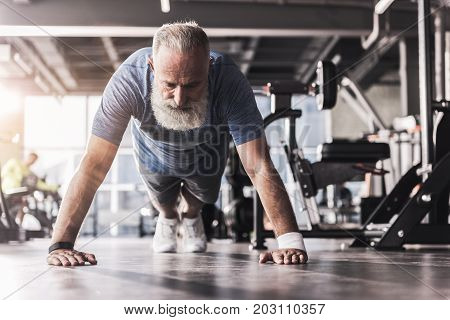 Full of energy. Concentrated senior man is doing push-ups. He is doing exercises on floor in modern gym with sports equipment on background. Low angle