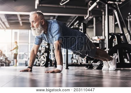 Perfect workout. Full-length of stylish bearded senior male in sportswear is doing push-ups in gym with professional equipment on background. Low angle