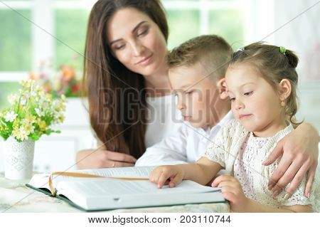 Mother and children sitting at table and reading interesting book