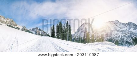 Stunning winter panorama with the peaks of the Austrian Alps mountains the evergreen fir forests and an alpine road all covered in snow in Ehrwald Austria.