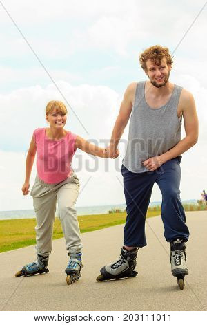 Active holidays exercises relationship concept. Young man dressed in sports clothes putting his girlfriend up to do rollerblading while holding her hand on promenade
