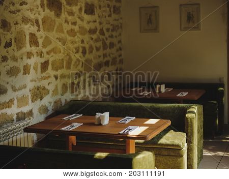 Gorgeous interior of a classic, vintage cafe with a brick wall, decorative pictures, wooden tables, retro sofas. Bistro indoors on a light background. Restaurant or cafeteria furniture concept.