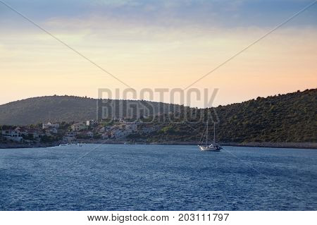 Sailboat in blue bay with romantic town on island. Luxury sail yacht in azure sea on roadstead.