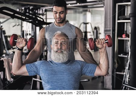 I am strong. Portraot of stylish old bearded man is sitting in modern gym and raising dumbbells over his head. His young trainer is touching his elbows while standing behind him