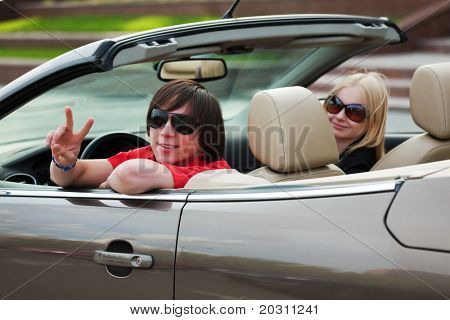 Happy young couple in a convertible car.