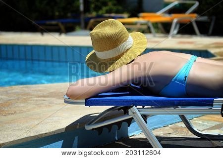 Young beautiful blonde girl sunbathing on a summer day on a lounger by the pool.