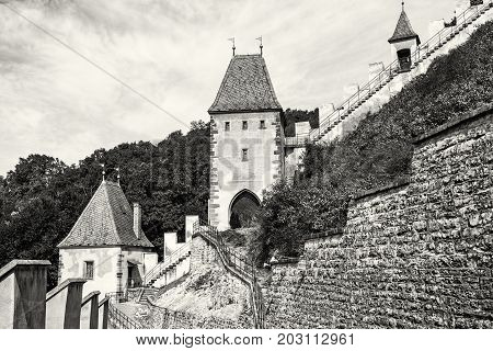 Gothic castle Karlstejn in Czech republic. Ancient architecture. Travel destination. Walls and turrets. Black and white photo.