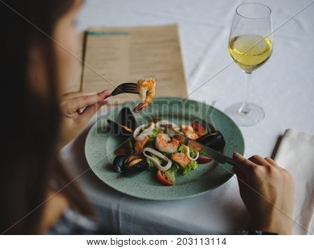 Close-up picture of a young woman eating shrimps, mollusks and spicy greens with knife and fork. A plate of healthy, salty seafood and a glass of wine on a blurred table background.
