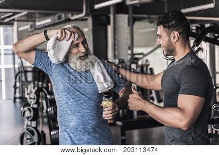 Enjoying conversation. Joyful men are talking in sport club with smile. Mature man is wiping his brow with towel while young guy is touching his shoulder and showing thumbs up