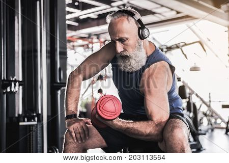 Music helps. Concentrated old bearded man is sitting on bench and doing exercises with dumbbell while listening to music in modern gym