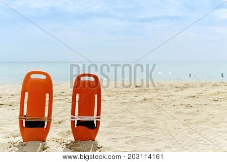closeup of some colorful rescue buoys in the sand of a quiet beach in the Mediterranean sea, with a negative space on top
