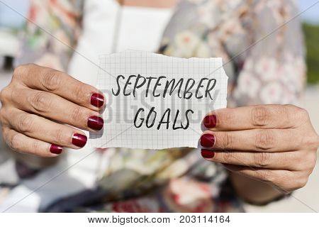 closeup of a caucasian young caucasian woman outdoors, with her nails painted red, showing a note with the text september goals written in it