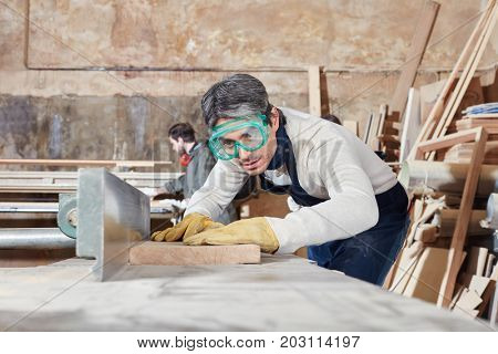 Carpenter concentrated on planing machine work at carpentry shop
