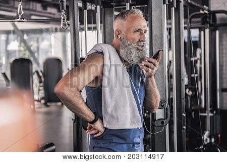 Always in touch. Concentrated old man is talking on smartphone using headset and expressing seriousness while standing in athletic center
