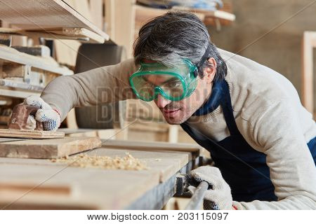 Joiner grinding wood with concentration