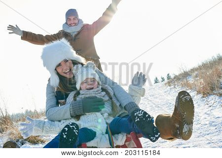 Family driving togobban in winter and having fun