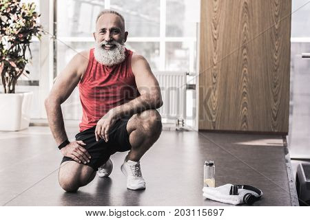 Always smile. Portrait of positive old bearded pensioner is looking at camera with joy while sitting on knee in light fitness center. Copy space in the right side