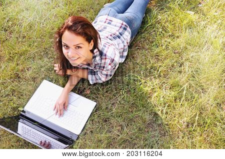 Top View Of Student Girl Working On Laptop, Lying On Grass In Park