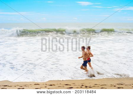 Couple Jogging On Th Beach