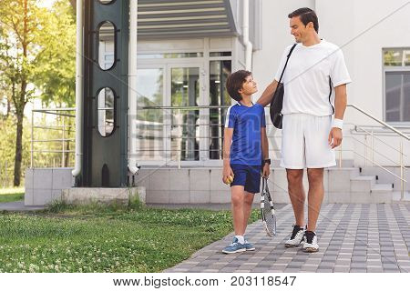 Confident son is walking beside father and holding tennis equipment. Joyous dad putting hand on his shoulder. Copy space on left side