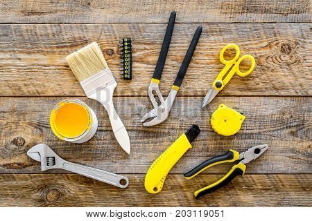 constructor desk with set of building implements and brushes on wooden desk background top view