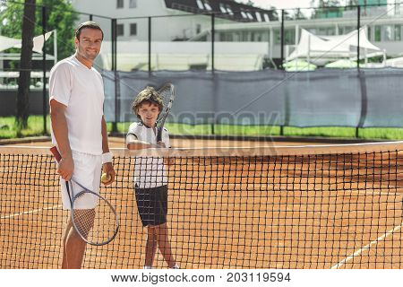 Cheerful father is holding racquet. Happy son locating near dad and looking at camera with smile. Full length portrait. Copy space on right side