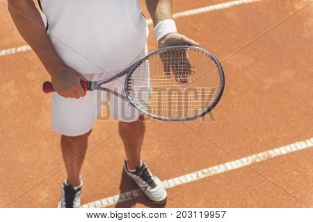Man is standing at tennis court and holding racquet. Top view. Focus on close up sport equipment in male hands. Copy space on right side