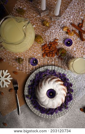 Top view of a table with a bunch of cinnamon, burning candles, almond, physalis, a glass of lemonade, a metal fork, a ring cake sprinkled with sugar powder on a light colorful background.