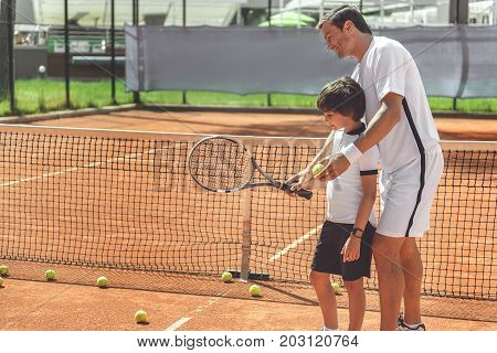 Happy dad is standing behind boy and showing right way of holding tennis racket. Copy space on left side. Profile