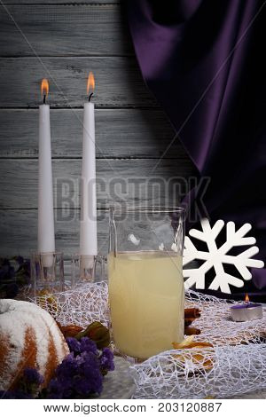 Two burning candles, a white snowflake, a ring cake sprinkled with sugar powder, silk violet curtain, lovely romantic evening at sunset with beloved people on a light gray wooden background.