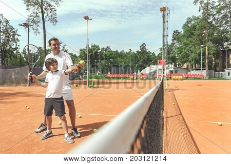 Glad father is standing near son and correcting his position with racket. They are going to make pitch. Full length portrait. Copy space on right side