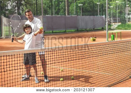 Joyous boy is holding tennis equipment and learning to play tennis. Proud father standing behind him. Full length portrait. Copy space on right side