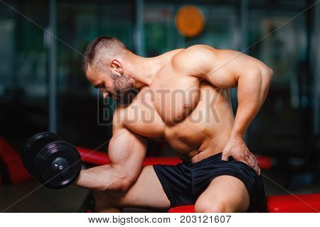 An attractive sportsman with an athletic body lifting a dumbbell in a gym on a light blurred background. Gym, sport, weight lifting, bodybuilding concept.