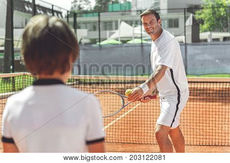Happy father is standing afore son on court and looking at him with smile. He going to make pitch. Full length portrait