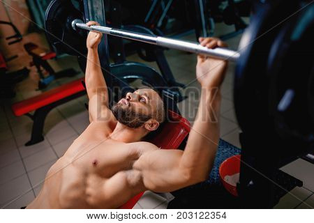 A sexy man with naked strong torso lifting a barbell on a blurred dark background. Gym, routine, training, workout, lifting concept.