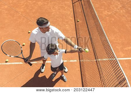 Father is teaching his son to make pitch in right way. He standing behind child near net at court. Top view. Copy space on right side