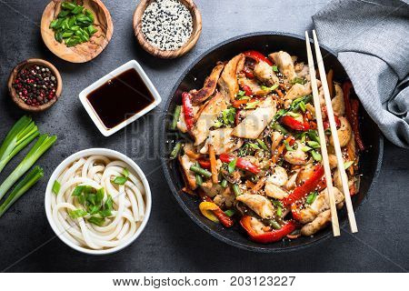 Chicken Stir fry, udon noodles and soy sause on black stone table. Traditional asian food. Top view.