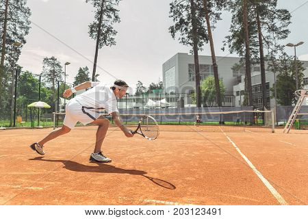 Man is going to beat off pitch. He using racket at court. Copy space on right side