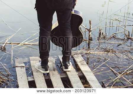 A young man in black clothes with a guitar in his hand is standing on a dilapidated bridge on the river bank