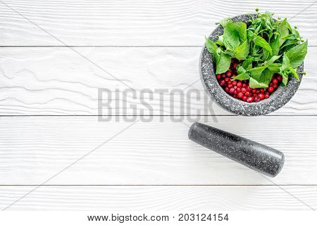 close up of ingredients for making spices and herbs in mortar on white wooden background top view mock up