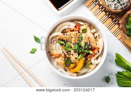Udon stir-fry noodles with chicken vegetables and sesame in white bowl. Traditional asian food. Top view copy space.