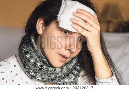 Sick woman caught cold and fever or headache bed at home. Apply the dressing wet to the head