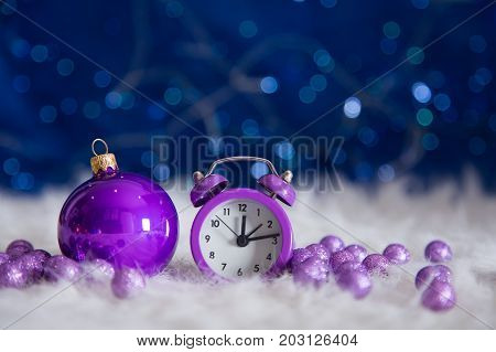 Purple Little Clock With Christmas Ball And Beads On Blue Bokeh Background