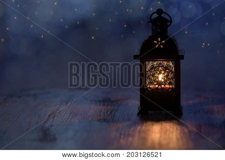 Lantern with candles and gold stars on a blue background. Beautiful background for the Christmas holidays