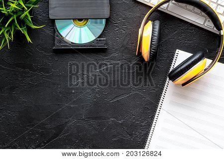 Headphone with paper note in music studio for dj or musician work on dark desk background top view mock-up