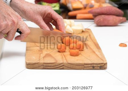 carrot being chopped on a wooden chopping board