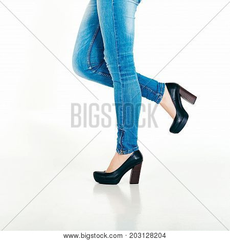 Woman's Legs In Blue Skinny Jeans And Black High Heels. Close Up Of Female Legs In Jeans And The Sho