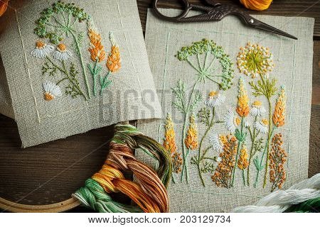 Beautiful embroidered work thread scissors wooden hoop on a wooden background