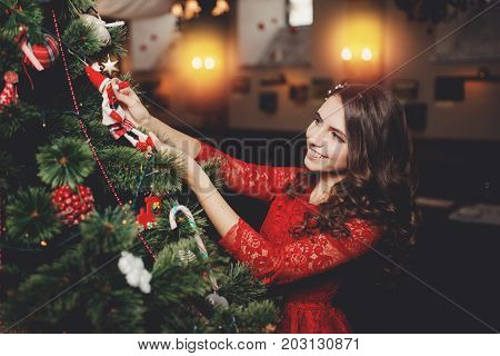 Girl is smiling decorating Christmas tree x-mas.