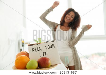 Close up of notebook with slogan 'Plan your life' between fruits. Laughing lady with smartphone